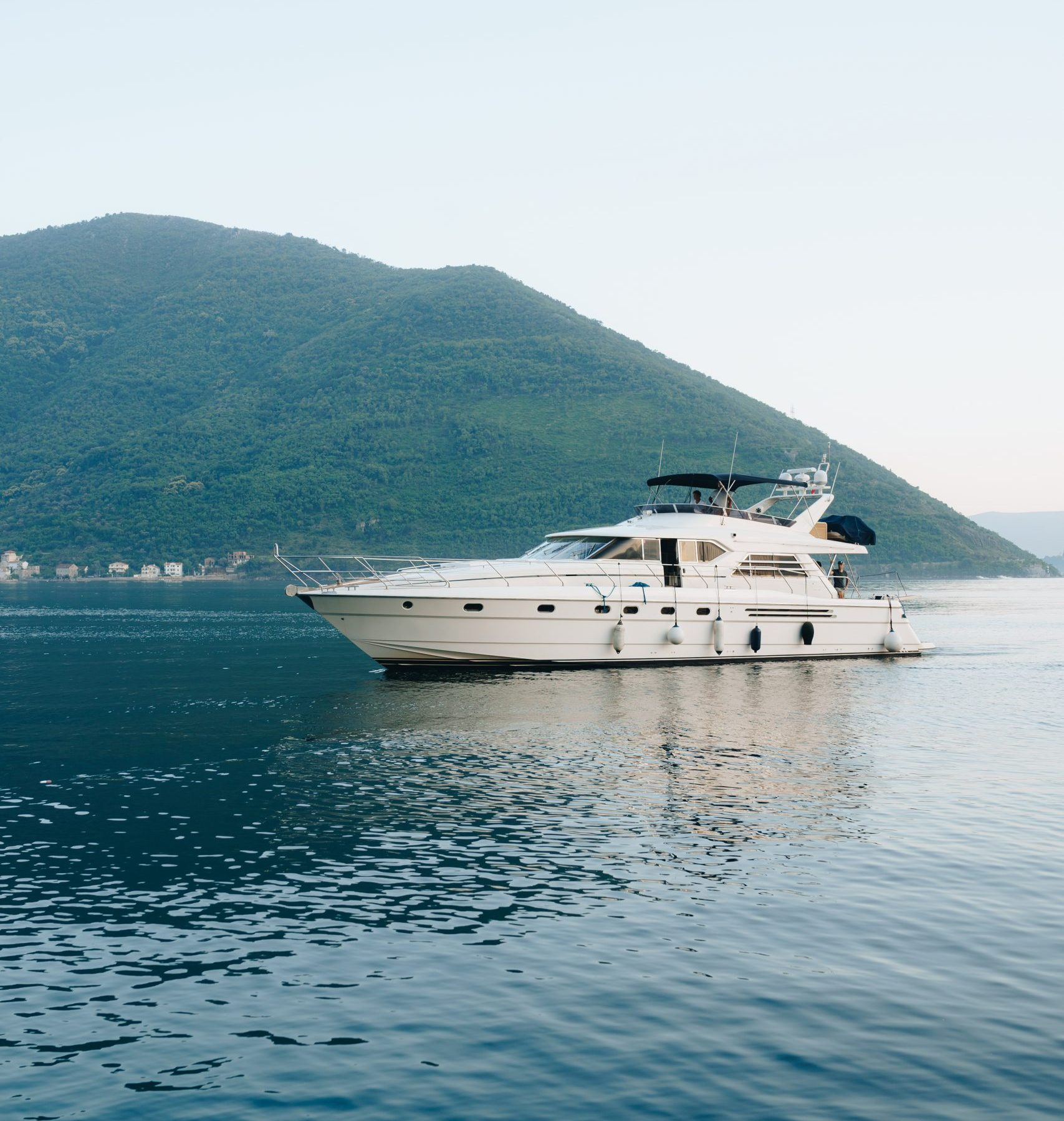 White cruise yacht on the water near the mountains in Montenegro. High quality photo